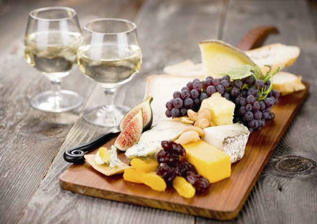 A delectable cheeseboard filled with an assortment of fine imported cheeses and served with dessert wine.  Shallow dof.